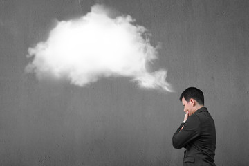 Businessman thinking about white cloud thought bubble with concr