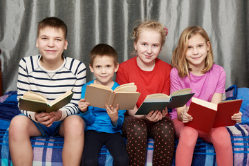 Children sitting and reading books at home