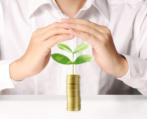 Man holding plant sprouting from a handful of coins