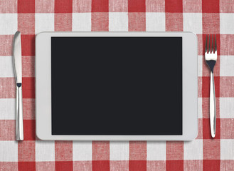 tablet pc, fork and knife on red checked tablecloth