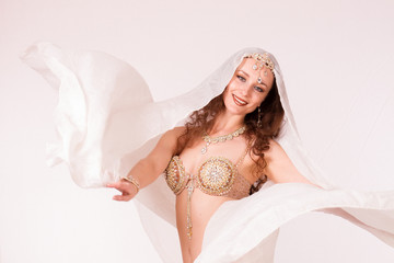 Bellydancer with veil smiling at camera