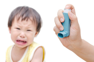 Woman's hand holding asthma inhaler foreground and crying baby s