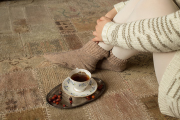 Woman next to tea cup on carpet
