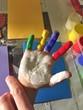 Bunte Hand vom Kind mit Fingerfarbe