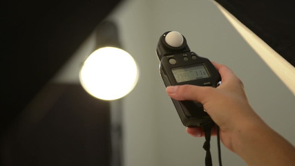 Person in photography studio with camera lenses using flash