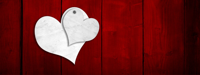 Conceptual two white old paper vintage hearts on red wood