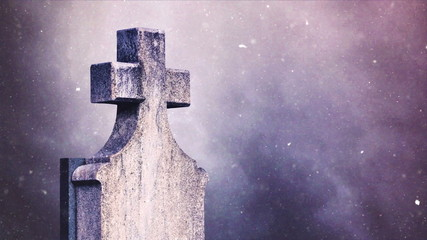 Cross on the cemetery during snowfall