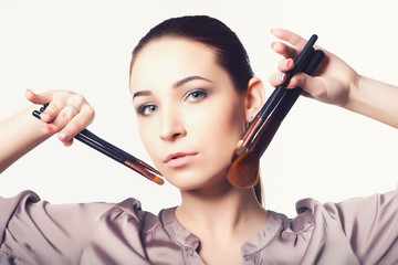 girl holding a set of professional makeup brushes.