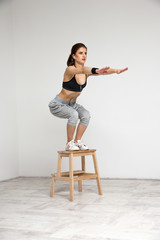 Young healthy woman doing squat exercises