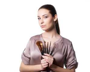 woman holding different make-up brushes.