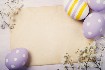 Colorful Easter eggs and flowers on old sheet of paper with spac