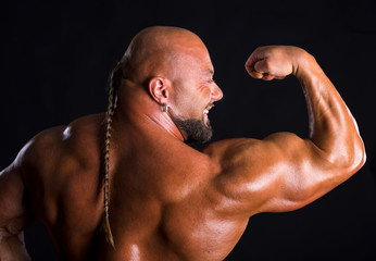 Bodybuilder  demonstrating muscles of the back and arms