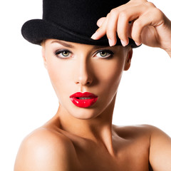 Fashion portrait of a beautiful young girl wearing a black hat.