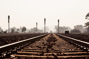 Distant man walking on railway track