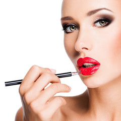 Woman applying red lipstick with cosmetic pencil on the lips