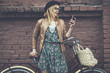 City lifestyle stylish hipster girl with bike using a phone text - 77870356