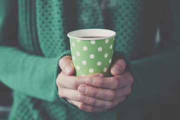 hands holding paper cup with take-out coffee