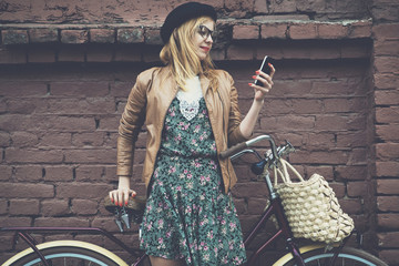City lifestyle stylish hipster girl with bike using a phone text