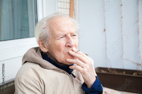 old man smoking a cigarette - 77871386