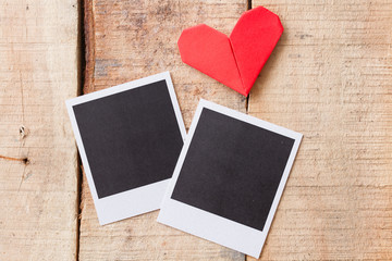 Instant photos with origami hearts. On wooden background