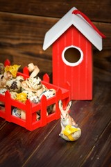 Easter decorations. Bunny with egg against bird-house