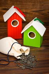 Green and red bird houses with seeds on wood