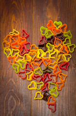 Macaroni forming a heart over wooden background.