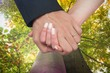Composite image of newlyweds holding hands close up
