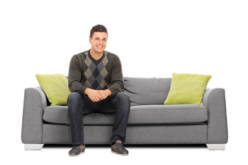 Cheerful young man sitting on a modern sofa