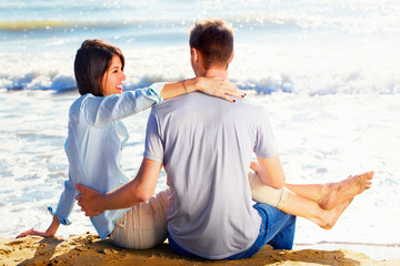 Couple Sitting on Sand at the Beach looking the sea