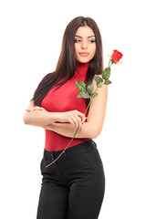 Vertical shot of an attractive woman holding a red rose