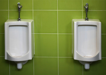 Urinals on green wall
