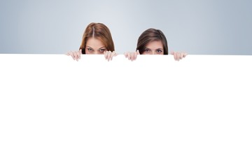 Two friends secretly hiding behind a blank poster