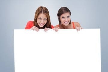 Teenage girls smiling while holding a blank poster