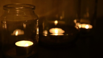 Small tea light candles burning in glass jars at night