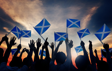 Group of People Waving Scottish Flags Back Lit Concept