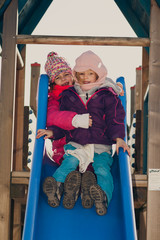 Two young girls playing on a slide on the playground