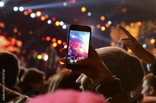 Leinwanddruck Bild People holding their smartphones and photographing concert