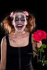 irrer Clown mit roter Rose vor schwarzem Hintergrund