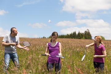 drei Personen spielen Badminton im Freien