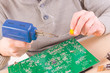 Leinwanddruck Bild - Serviceman soldering on PCB