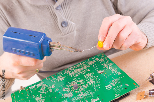 Serviceman soldering on PCB - 77879123