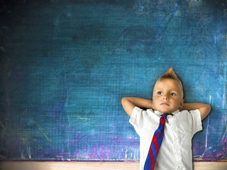 little schoolboy with blackboard in background
