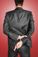 Liar businessman cross his finger, red background