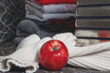 Stack of books with glossy edge and red apple