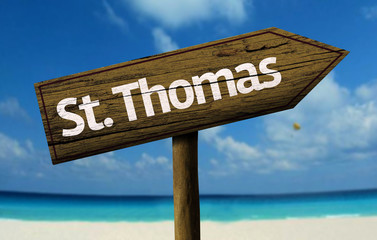 St. Thomas wooden sign with a beach on background