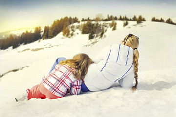 mother and doughter resting on the snow, looking at sunset
