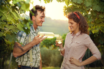 farming couple drinking a glass of wine after the harvest