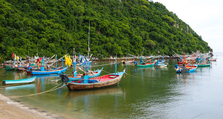 GROUP OF FISHING BOAT NEAR A MOUNTAIN