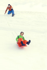 little boy sledding very fast pushed by his father